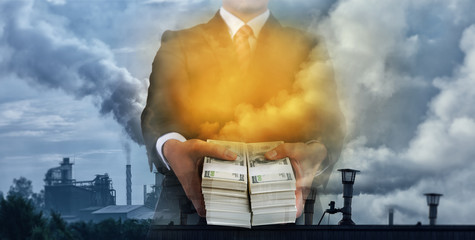Businessman with dollars on hand with poor environment from industrial background.Corruption concept.