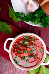 Ukrainian traditional borsch. Russian vegetarian red soup  in white bowl on red wooden background. Top view.  Borscht, borshch with beet.