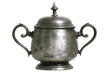 An old silver metal sugar bowl with a lid and ornament. Metal punctles with scratches and patina.