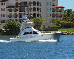 Charter fishing boat passing luxury condominium buildings on its way back to port through Government Cut in Miami,Florida.