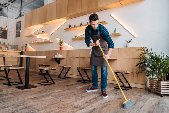 worker cleaning floor with sweep