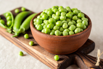 Fresh green peas in ceramic bowl on gray stone background