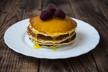 stack of pancakes with honey and raspberry on white plate