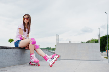 Portrait of an attractive young woman in shorts, t-shirt, sunglasses and rollerblades sitting on the concrete bench in the outdoor roller skating rink.