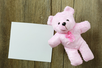 Teddy Bear is placed on old brown wood floor.