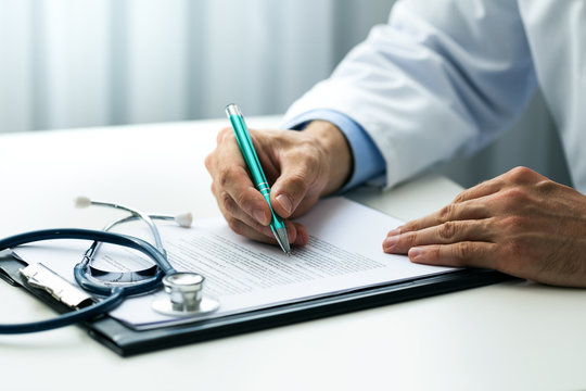 doctor writing documents at desk in clinics office