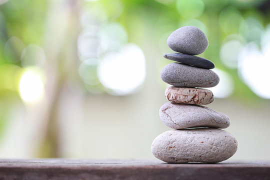 Balance Stones stacked to pyramid in the soft nature green background.