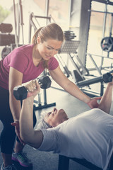 Personal trainer working exercise with senior woman in the gym. Woman lift weight. Workout in gym.