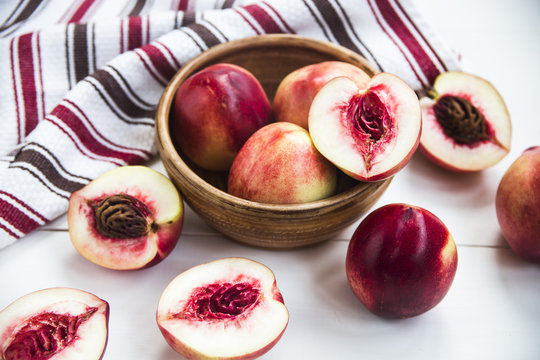 Ripe nectarines in a clay dish white table