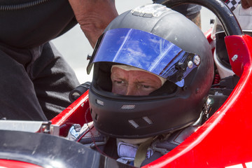 Man in IRL race car with helmet
