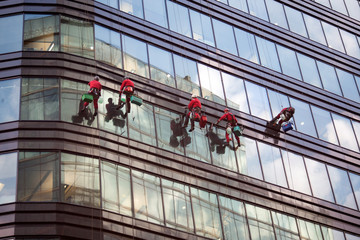 Group of workers cleaning windows service on high rise building. Image with GPS tags.