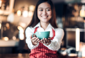 Close up on coffee up with blur asian woman barista holding mug with two hand with smiling face at cafe bar background,Focus on coffee up