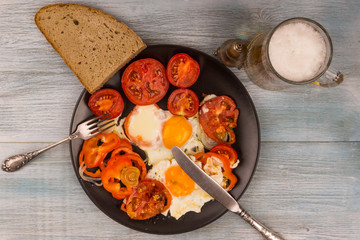 Rural breakfast - fried eggs and tomatoes and beer on a rustic wooden background