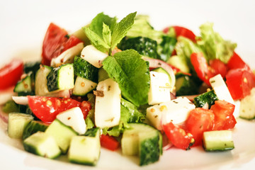 Salad of cucumbers, tomatoes, mozzarella cheese, lettuce, onions, spices and olive oil. Healthy food. Tomato, cucumber, mozzarella cheese, onion, lettuce.