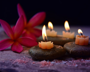 Soft Light and candles scented with refreshing fragrance and salt scrub on black stones, including plumeria flower, spa concept, Thai massage on black background.