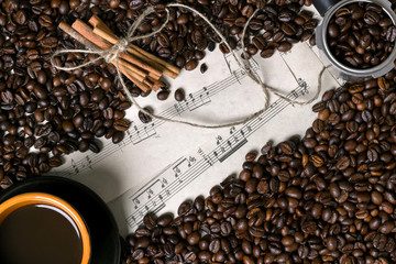 Coffee beans, cinnamon sticks and cup of brewed coffee on sheet music background, view from above with space for text