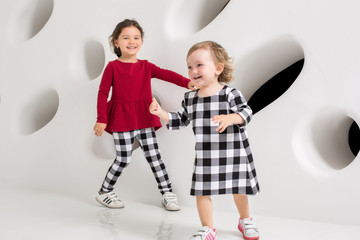 Two stylish little girls run after each other on white wall background
