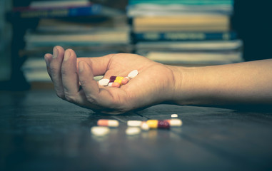 The man committing suicide by overdosing on medication. Close up of overdose pills and addict.