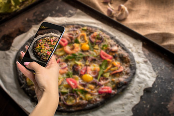 Photographing food concept - woman takes picture of italian pizza with black dough and seafood on a baking tray from the oven