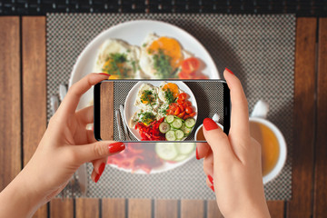 Woman hands taking photo of breakfast with smartphone