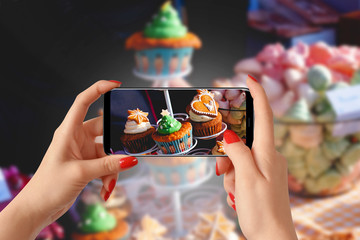 Woman hands taking photo of cupcakes with smartphone