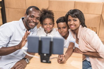 happy african-american family taking selfie in cafe