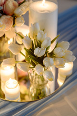 Fresh spring tulips and candles in glasses. Covered festive tabl