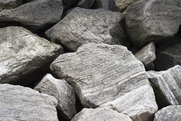 A group of gray rocks found by the coast create a patterned, abstract design.