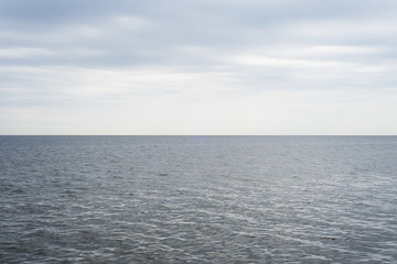 The calm blue-gray ocean waters meet the cool, cloudy blue overcast sky, with a perfectly straight...