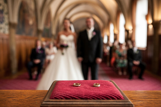 Wedding rings in front of bride and groom