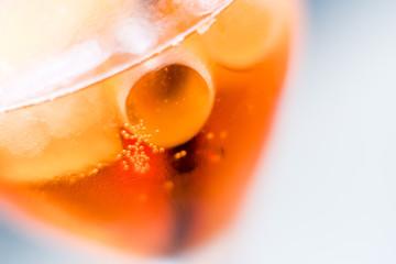 Nahaufnahme von Eiswürfel in einem Glas mit orangefarbenem Drink