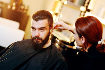 Beautiful manly bearded man in a barbershop on a beard styling