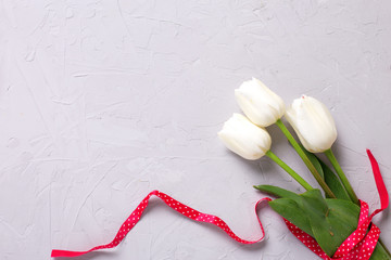 Bunch of white tulips flowers with  red  ribbon on  grey textured  background.