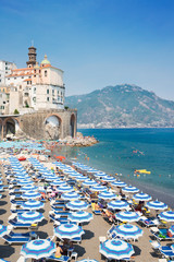 Amalfi town and summer Atrani beach with umbrellas , Italy