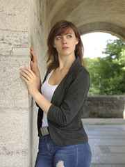 Junge Frau angelehnt an eine Wand