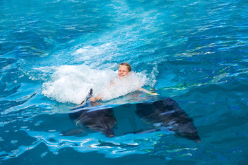 Happy child and dolphins in blue water. Dolphin Assisted Therapy