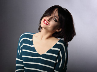 Beautiful happy smiling enjoying woman shaking her short black hairstyle with red lipstick on grey background in fashion pullover