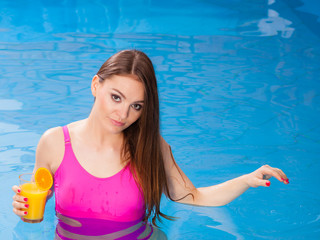 Girl relaxing at swimming pool with drink