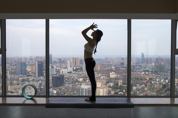 young asain woman doing yoga by the window