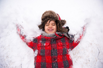 child attempting to make a snow angel