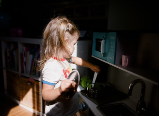 little girl cooks in play kitchen