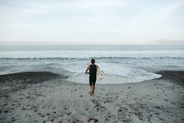 Mature surfer man heading into the water