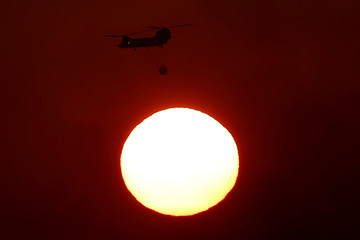 A Chinook helicopter flies over the setting sun as a wildfire burns near the village of Kapandriti