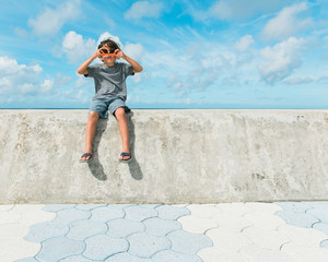 boy sits on sea wall looking through sunglasses backwards