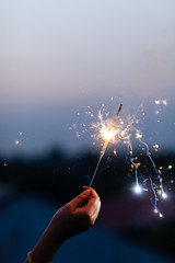 Woman's hand holding sparkler to the sky at twilight