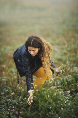 Portrait of curly brunette bending down to collect flowers in field