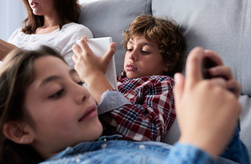 Family reading books via tablets on sofa at home