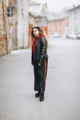 Beautiful young curly long haired woman wearing street style outfit in urban street