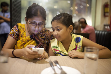 Teenage girl and Adult Woman browsing and texting smartphone in a restaurant