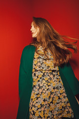 young woman with flower pattern dress and a green coat